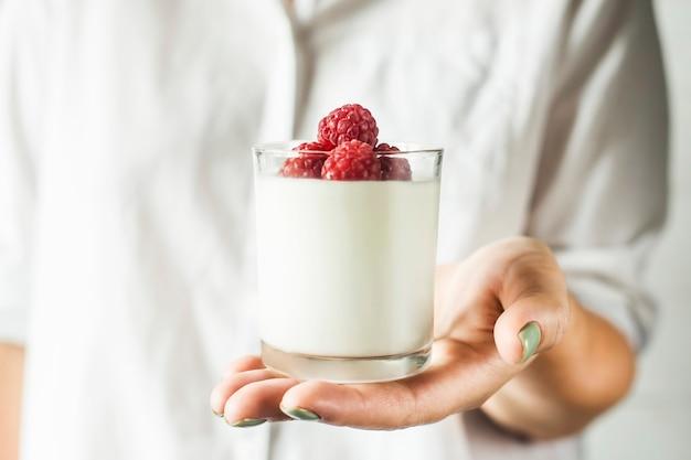 Un barattolo di vetro con yogurt fatto in casa con lamponi nelle mani di una donna