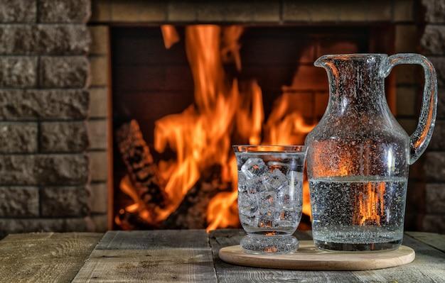 Un barattolo e un bicchiere di acqua minerale con ghiaccio davanti al caminetto acceso in una casa di campagna, copia spazio.