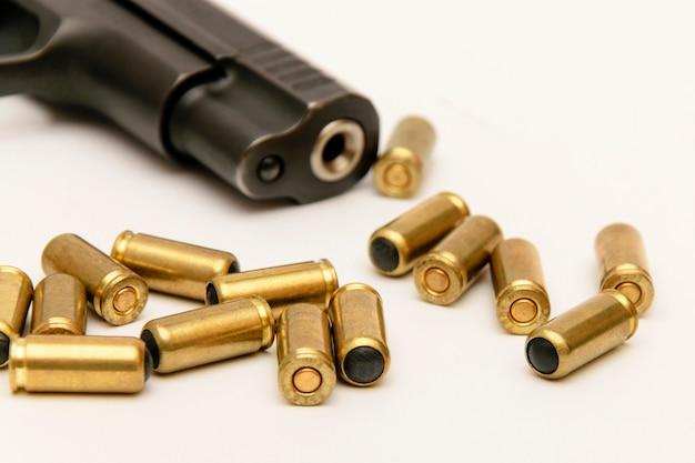 Un barile di pistola e proiettili d'oro su uno sfondo chiaro di close-up