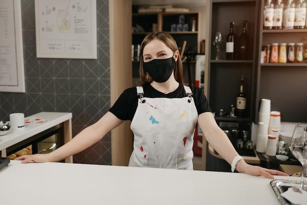 Un barista femmina felice in una maschera medica nera sorride e aspetta i clienti nella caffetteria. una bella proprietaria del caffè si pone con le braccia divaricate dietro il bancone.