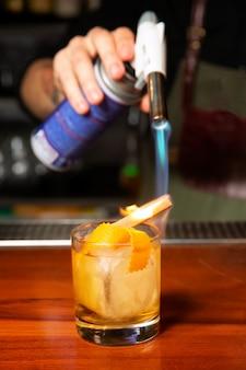 Un barista maschio brucia un bastoncino di cannella con un bruciatore a gas in un bar. processo di preparazione di un cocktail.