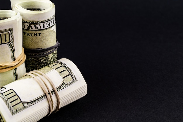 Un batuffolo di denaro in un carrello del supermercato su fondo nero