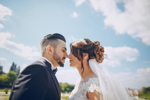 Un bel giovane che indossa un abito nero e una barba nel parco insieme alla sua sposa