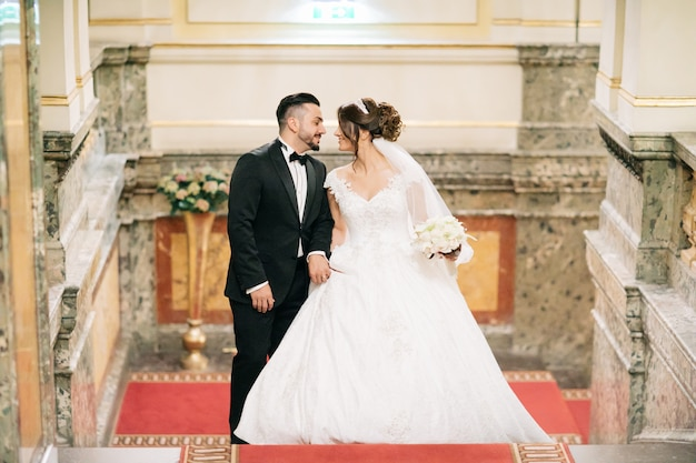 Un bel giovane che indossa un abito nero in piedi con la sua sposa