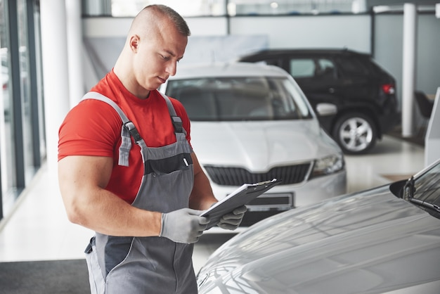Un bel giovane parla in una concessionaria di auto, riparando un'auto in un'officina.