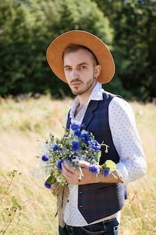 Un bel giovane ragazzo con la barba e un cappello in campo con un mazzo di fiori
