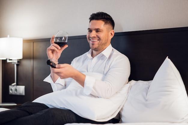 Un bel giovane uomo d'affari che beve vino rosso a letto e guardare la tv e ridere