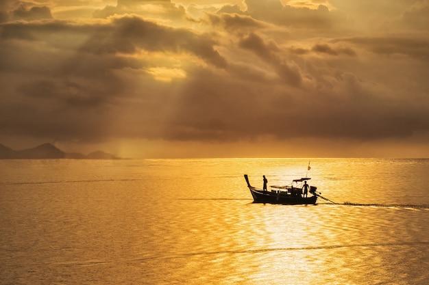 Un bel tramonto dorato sul mare, pescatore asiatico sulla barca di legno con tempo di tramonto