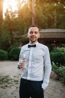 Un bell'uomo in camicia bianca e cravatta assaggia vino bianco da un bicchiere trasparente.