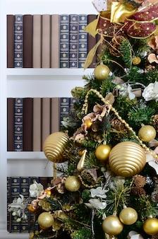 Un bellissimo albero di natale decorato sullo sfondo di una libreria con molti libri