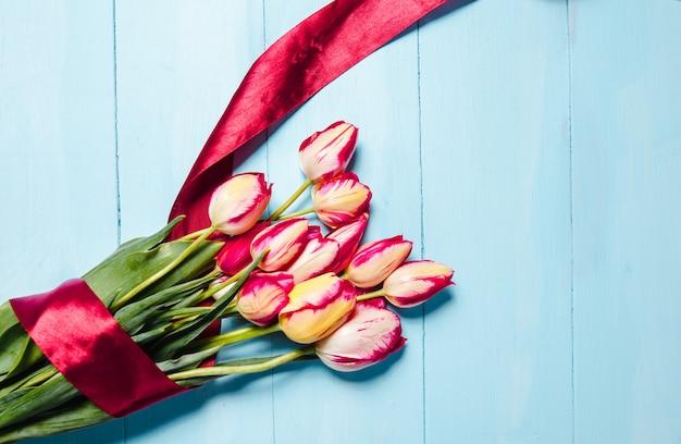 Un bellissimo bouquet di tulipani rossi su sfondo blu