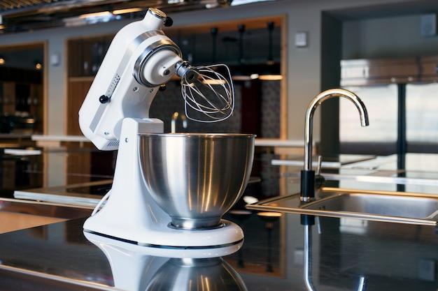 Un bellissimo mixer bianco con una tazza di metallo