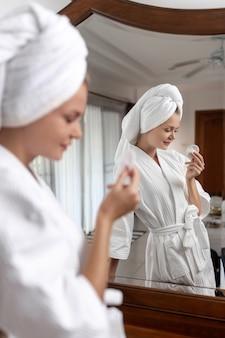 Un bellissimo modello sorridente pone in un accappatoio bianco con un turbante in testa in bianco con un batuffolo di cotone in mano. cura
