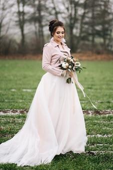 Un bellissimo ritratto della sposa in un abito elegante con un bouquet invernale di rose, cotone e abete rosso contro un campo verde con il primo. foto del matrimonio