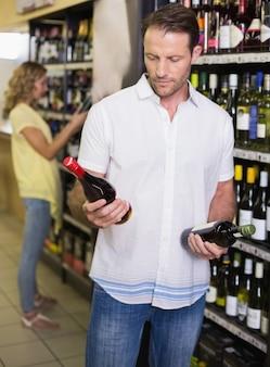 Un bello che mostra una bottiglia di vino