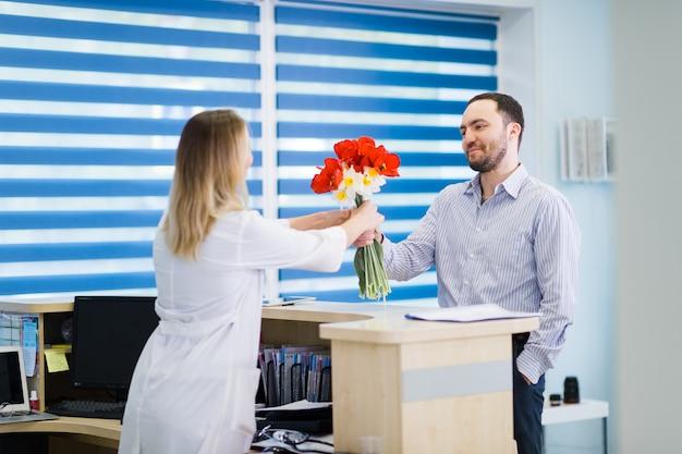 Un bello giovane medico che cattura il mazzo dei fiori dal giovane paziente maschio riconoscente