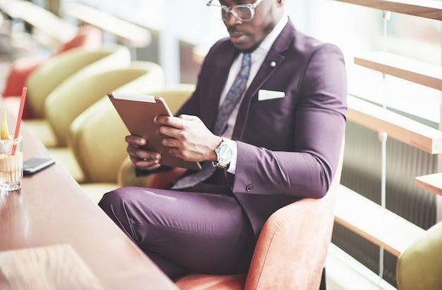 Un bello uomo d'affari afroamericano legge in un caffè.