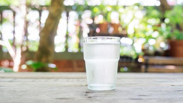 Un bicchiere d'acqua su un tavolo di legno.
