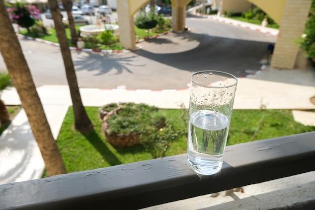 Un bicchiere d'acqua sul balcone della camera d'albergo. il resto è tutto compreso.