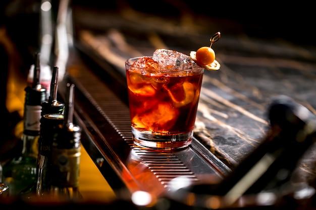 Un bicchiere da cocktail con cubetti di ghiaccio, guarnito con frutta secca e limone