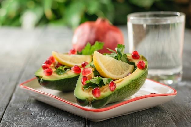 Un bicchiere di acqua pulita con metà di avocado riempito con semi di melograno ed erbe. cucina vegetariana per dimagrire.