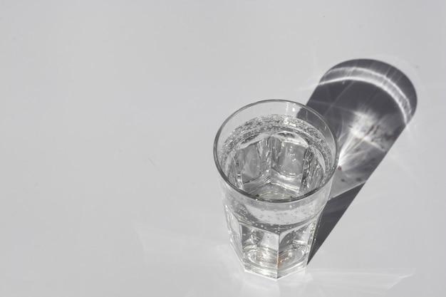 Un bicchiere di acqua pura sotto la luce del sole con ombre alla moda profonde copyspace