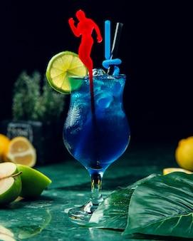 Un bicchiere di bevanda blu con ghiaccio guarnito con fetta di lime