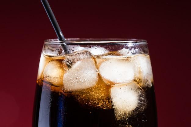 Un bicchiere di bibita cola con un sale, su un rosso,
