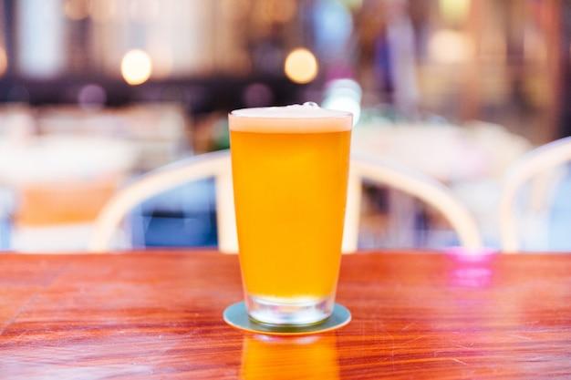 Un bicchiere di birra alla spina con schiuma sul bancone in legno con sfocatura e bokeh sfondo.