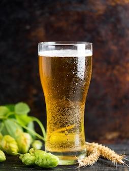 Un bicchiere di birra chiara su uno sfondo arrugginito scuro con luppolo verde