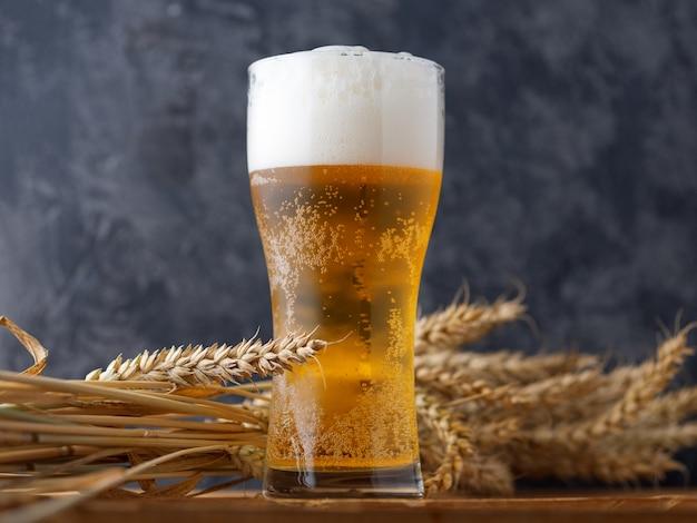 Un bicchiere di birra contro un muro scuro