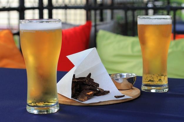 Un bicchiere di birra leggera spumosa e uno spuntino con crostini di pane sul tavolo del bar.
