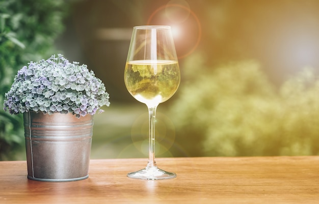 Un bicchiere di champagne e un piccolo vaso su un tavolo di legno con un giardino come sfondo sfocato.