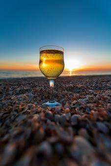 Un bicchiere di champagne sulla costa si erge sulla sabbia contro il tramonto