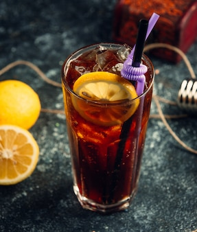 Un bicchiere di coca-cola con cubetti di ghiaccio e fetta di limone a sfondo grigio