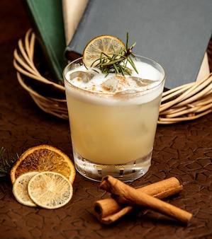 Un bicchiere di cocktail con ghiaccio guarnito con limone essiccato e rosa marina