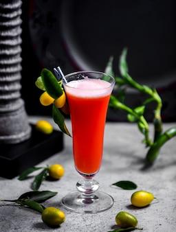 Un bicchiere di cocktail di frutta guarnito con kumquat