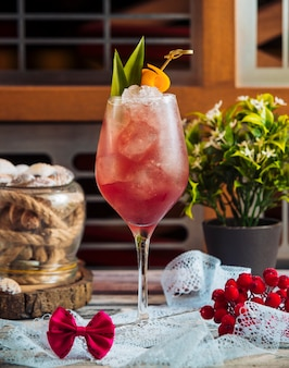 Un bicchiere di cocktail rosso con cubetti di ghiaccio e foglie verdi.