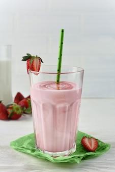 Un bicchiere di frullato di latte alla fragola. frullato di fragola sano in un bicchiere con frutti di bosco. cocktail proteico con sciroppo di fragole, bacche e cannucce di carta verde.