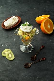 Un bicchiere di frutta mista con panna