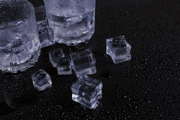 Un bicchiere di ghiaccio e ghiaccio si trova su uno sfondo nero
