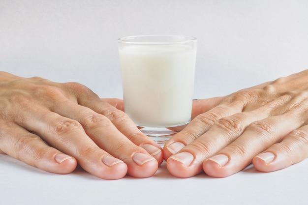 Un bicchiere di latte biologico su una superficie bianca.