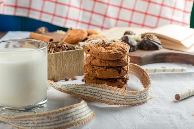 Un bicchiere di latte con biscotti di farina d'avena intorno