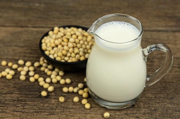 Un bicchiere di latte di soia con semi di soia sul fondo della tavola in legno.