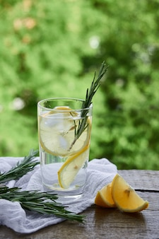 Un bicchiere di limonata fredda, spicchi di limone su uno sfondo di fogliame verde