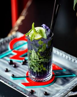 Un bicchiere di mojito viola con fiori viola lime e menta