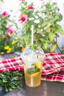 Un bicchiere di plastica con un tubo con mojito con menta e limone sul tavolo