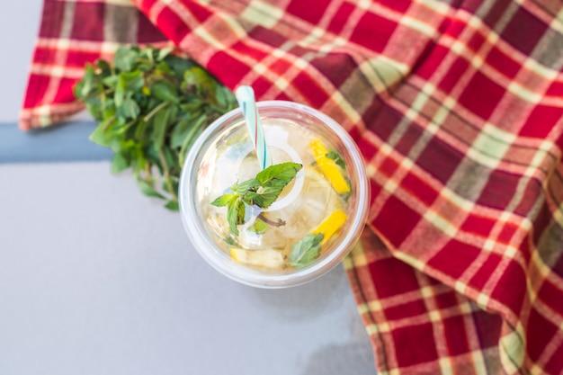 Un bicchiere di plastica con un tubo di mojito con menta e limone sul tavolo