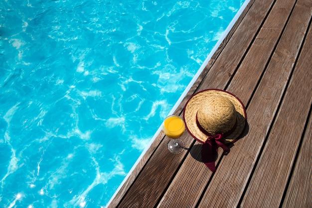 Un bicchiere di succo con cappello vicino piscina