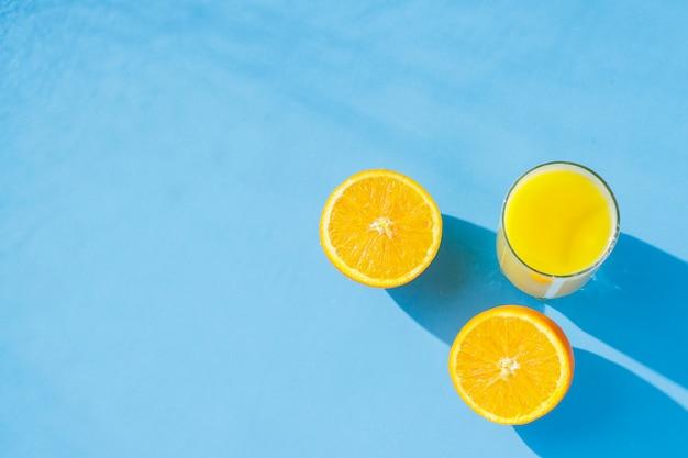 Un bicchiere di succo d'arancia e arance su sfondo blu. concetto di vitamine, tropici, estate. luce naturale. vista piana, vista dall'alto.